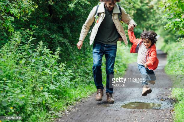 jumping in puddles - son stock pictures, royalty-free photos & images