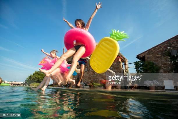 saltar en el aire - pool party fotografías e imágenes de stock