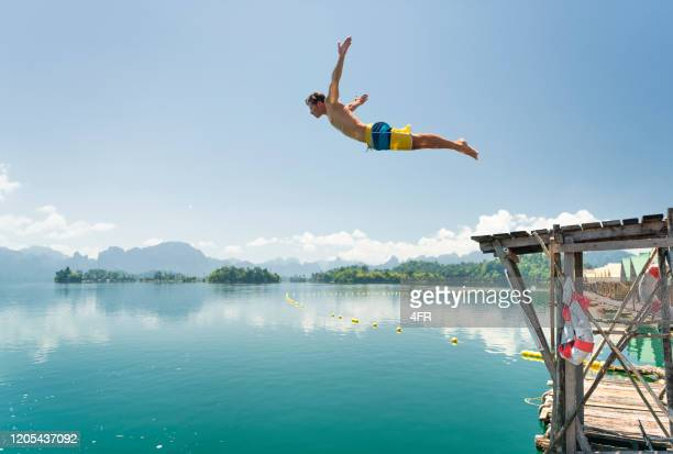 jumping in the clear lake ratchaprapha, khao sok national park, thailand - diving into water stock pictures, royalty-free photos & images