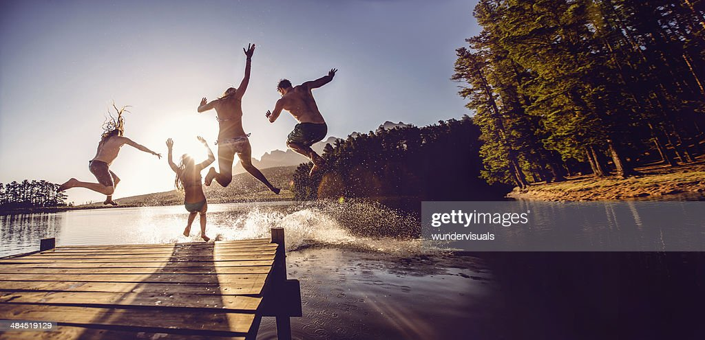 Jumping into the water from a jetty : Stock Photo