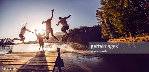 jumping into the water from a jetty - lake stock pictures, royalty-free photos & images
