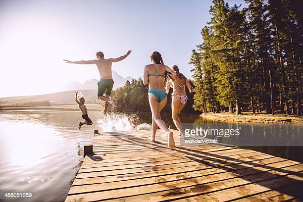 jumping into the water from a jetty - jetty stock pictures, royalty-free photos & images