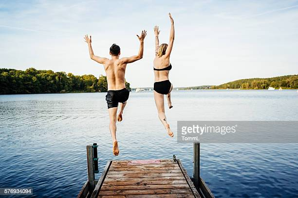 jumping into the water from a jetty - jumping stock pictures, royalty-free photos & images