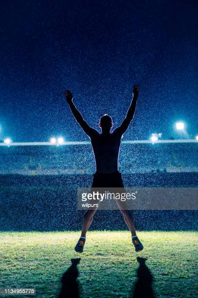jumping jack warm up in the rain at night - famous footballers silhouette stock pictures, royalty-free photos & images