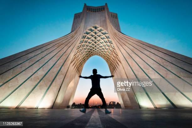 a jumping man under azadi tower, teheran, iran - tehran stock-fotos und bilder