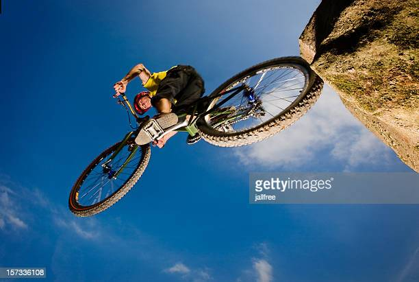 jumping off a rock on a mountain bike