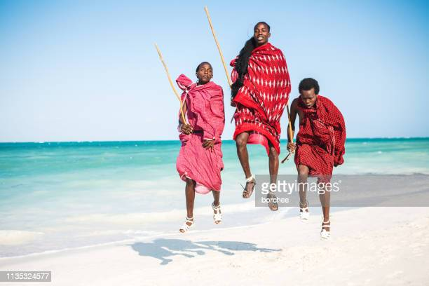 jumping on the beach - african tribal culture stock pictures, royalty-free photos & images