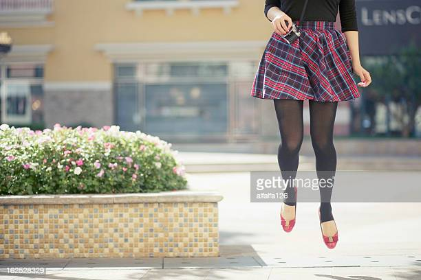 jumping - girls in plaid skirts stock photos and pictures