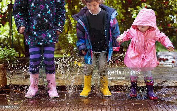 jumping puddles - charco fotografías e imágenes de stock