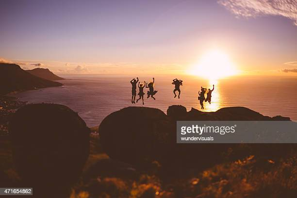 Jumping silhouettes in front of a sunset over the sea