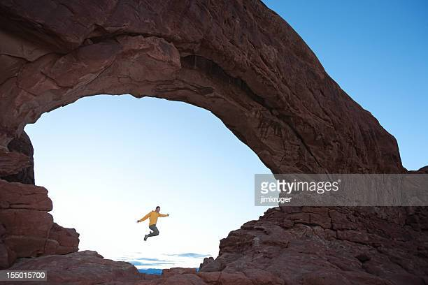jumping through the north window at arches national park. - leap of faith stock photos and pictures