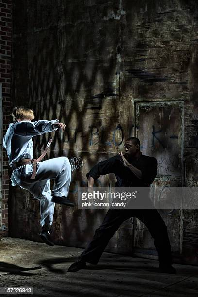 jumping up to kick in kenpo karate with uniforms - black alley stock photos and pictures