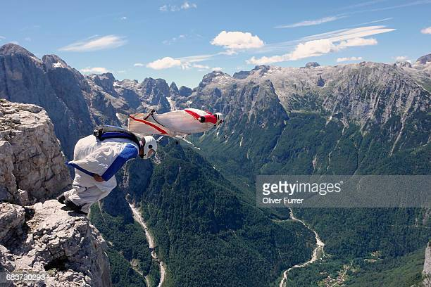 base jumping wingsuit pilots are jumping together from a cliff and down the valley, italian alps, alleghe, belluno, italy - friendly match stockfoto's en -beelden