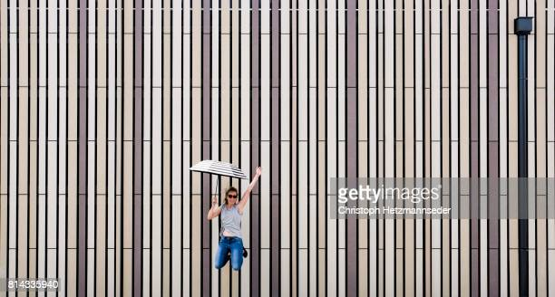 jumping woman with open umbrella - free walpaper stock photos and pictures