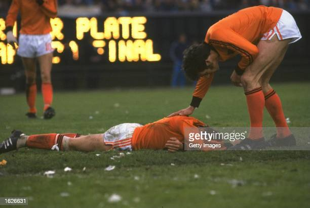 A Dutch player lies distraught whilst his team mate tries to console him after the World Cup final between Holland and Argentina at the Monumental in...