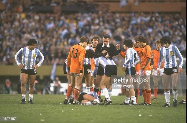 Gonella the referee of Italy looks at his watch as an Argentinan player lies injured on the ground during the World Cup Final match between Argentina...