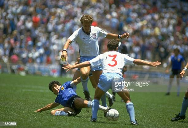 Diego Maradona of Argentina slides in to tackle Terry Butcher of England as Kenny Samson also of England blocks during the World Cup quarterfinal at...