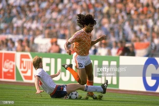 Mark Wright of England slides in to tackle Ruud Gullit of Holland during the European Championship match against England at the Rheinstadion in...