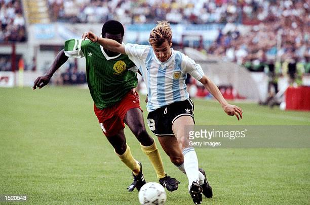 Claudio Caniggia of Argentina is shadowed by Benjamin Massing of Cameroon during the World Cup first round match at the Giuseppe Meazza Stadium in...