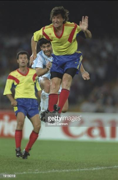 Diego Maradona of Argentina and L Rotario of Romania both jump for the ball during the World Cup match in Naples Italy The match ended in a 11 draw...