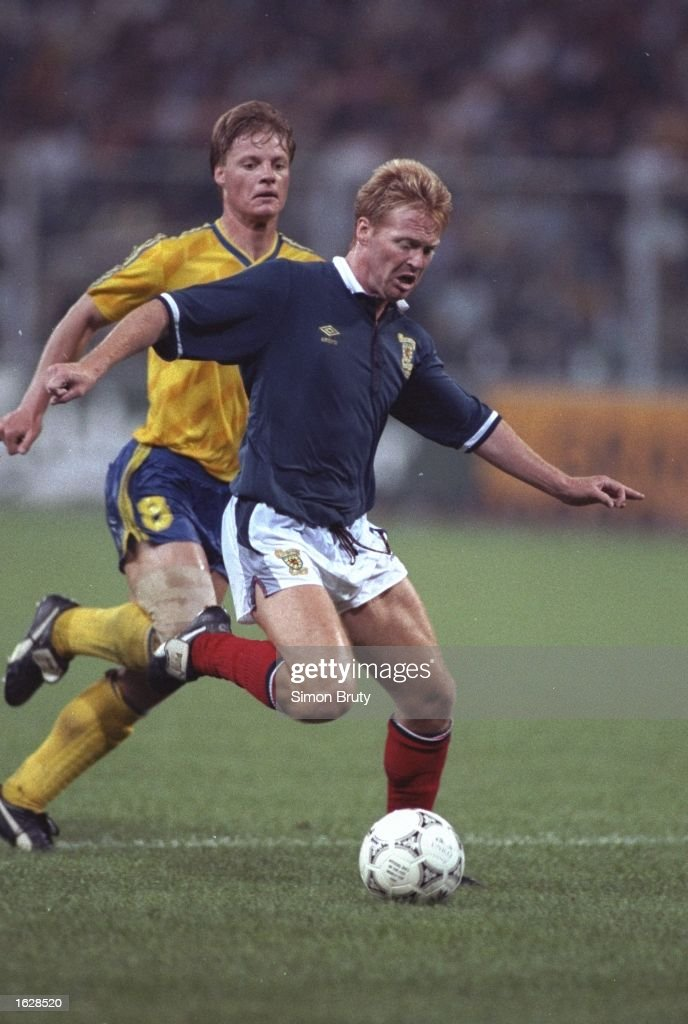 Mo Johnstone (right) of Scotland holds off Stefan Schwarz (left) of Sweden during the World Cup match in Genoa, Italy. Scotland won the match 2-1. \ Mandatory Credit: Simon Bruty/Allsport