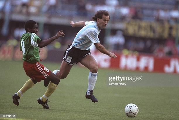 SH Calderon of Argentina evades the challenge of Emile Mbouh Mbouh of Cameroon during the World Cup match in Milan Italy Cameroon won the match 10...