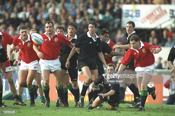 Ant Strachan of the New Zealand All Blacks passes the ball to his backs as forwards watch on during the first test against the British Lions in...
