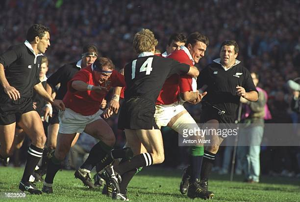 Ben Clarke of the British Lions drives forward helped by team mates Martin Johnson and Brian Moore as John Kirwin of the New Zealand All Blacks tries...