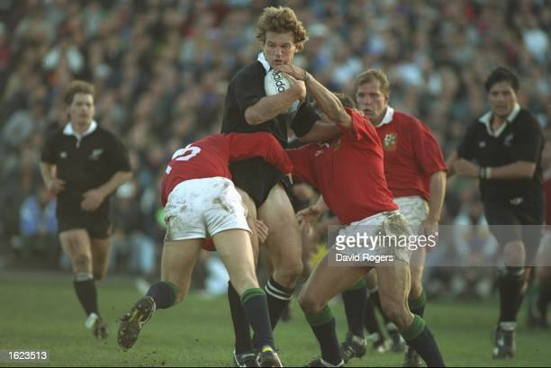 John Kirwin of the New Zealand All Blacks is tackled by Scott Gibbs and Rob Andrew of the British Lions during the second test in Wellington New...