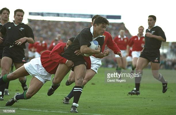 John Timu of the New Zealand All Blacks is tackled by Jeremy Guscott of the British Lions during the first test in Christchurch New Zealand New...