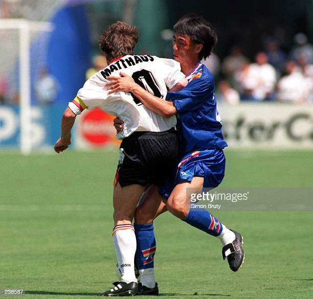 LOTHAR MATTHAEUS OF GERMANY IS GRABBED BY MYUNG BO HUNG OF SOUTH KOREA DURING GERMANY