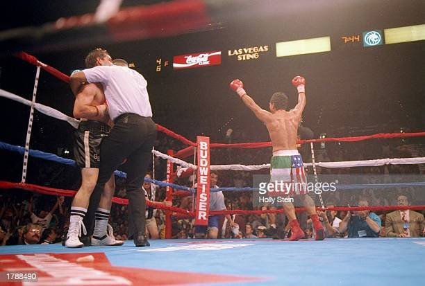 Tony Lopez raises his arms in the air as the referee holds Greg Haugen against the ropes during their fight in Las Vegas Nevada Lopez won the bout