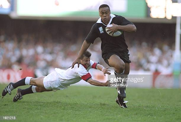 Jonah Lomu of New Zealand evades the diving tackle of Rob Andrew of England during the Rugby World Cup Semi Final at the Newlands Stadium in Cape...