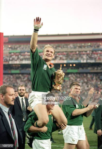 South African rugby captain Francois Pienaar is carried on Hennie Le Roux's shoulders with the William Webb Wellis Trophy after they defeated New...
