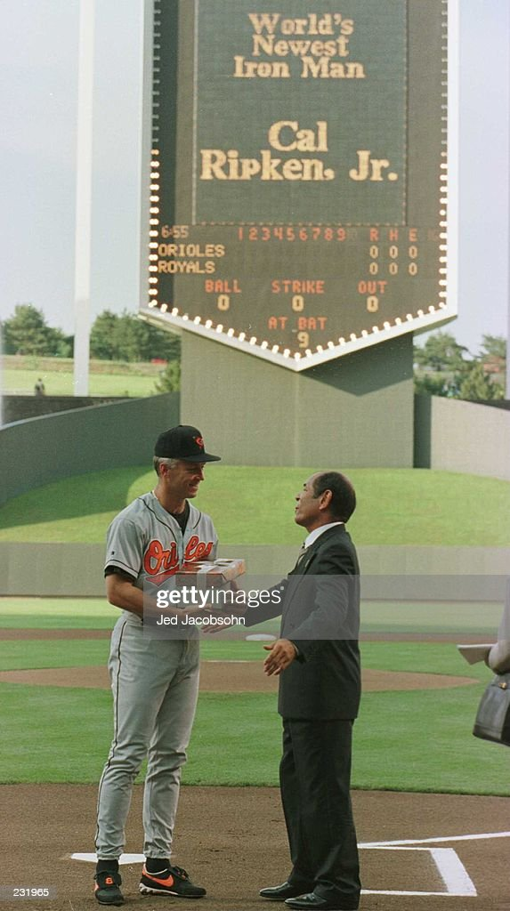 Baltimore Orioles Cal Ripken Jr. exchanges gifts with Japan''s Sachio Kinugasa, before breaking his all time record of consecutive games played standing at 2,216 , during the game against the Kansas City Royals at Kauffman Stadium in Kansas Ci