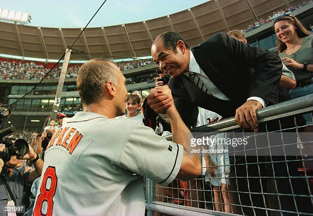 Cal Ripken Jr of the Baltimore Orioles is congratulated by Sachio Kinugasa of Japan after breaking his all time consecutive games played record of...