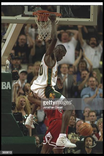 Forward Shawn Kemp of the Seattle SuperSonics dunks over Chicago Bulls forward Dennis Rodman during a game at the Key Arena in Seattle Washington The...
