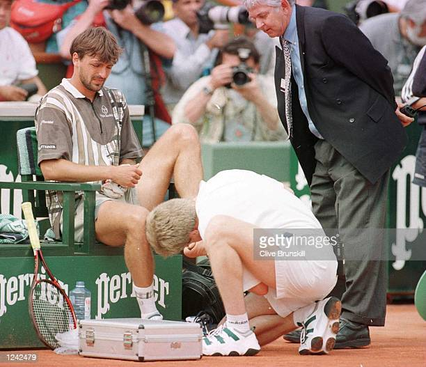 Goran Ivanisevic of Croatia is treated for a foot injury during today's straight sets defeat by Bernd Karbacher of Germany in the fourth round of the...