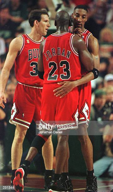 Guard Scottie Pippen of the Chicago Bulls celebrates with teammates Michael Jordan and Jud Buechler at the end of the first half of the third game of...