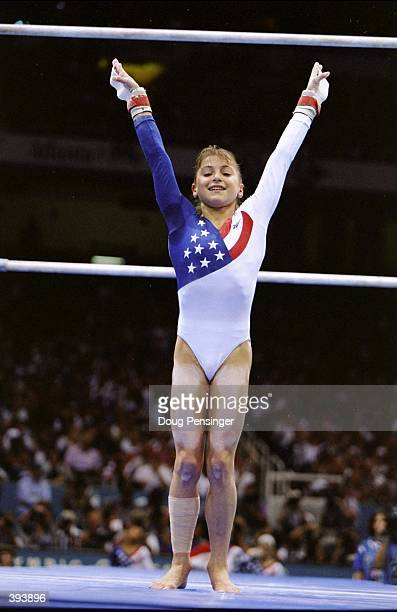 Gymnast Dominique Moceanu of the USA finishes the Parallel Bars in the Womens Team Option Competition during the 1996 Olympic Games at the Georgia...
