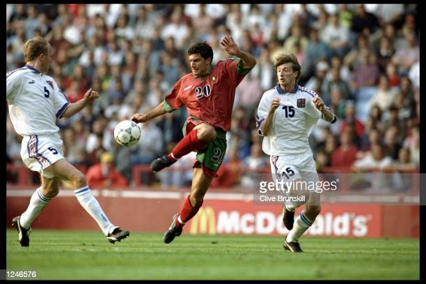 Luis Figo of Portugal attempts to play the ball but is pursued by Michal Hornak and Miroslav Kadlec both of the Czech Republic during the European...
