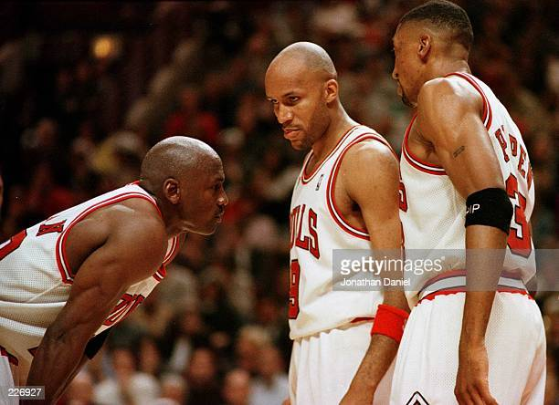Michael Jordan of the Chicago Bull left discusses strategy with teammates Ron Harper center and Scottie Pippen during a timeout on the court during...