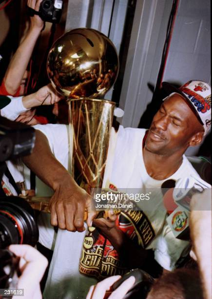 Michael Jordan of the Chicago Bulls celebrates with the NBA Championship trophy in the locker room afer the Bulls win game six of the NBA Finals at...