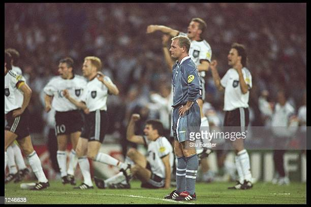 Paul Gascoigne of England expression tells the story as the Germans celebrate in the background during the European soccer championships semi final...
