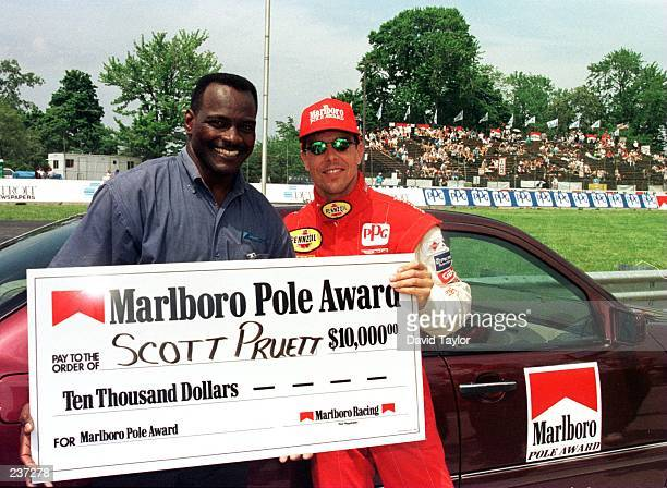 Scott Pruett in his Patrick Racing Lola Ford T96/00 is presented with the Marlboro pole position award check for $1000000 from former NFL star and...