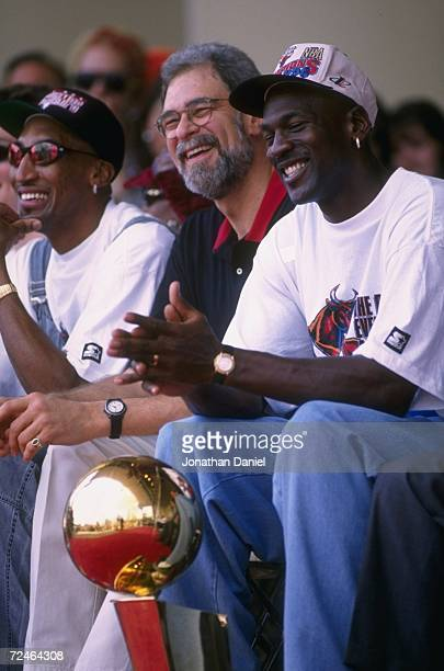 Scottie Pippen head coach Phil Jackson and Michael Jordan smile as they sit on the podium with the NBA CHampionship trophy during the Bulls victory...
