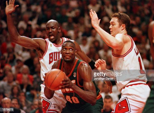 Seattle Supersonic Shawn Kemp works to the basket between Chicago Bulls Michael Jordan and Luc Longley during fourth quarter action of game six of...