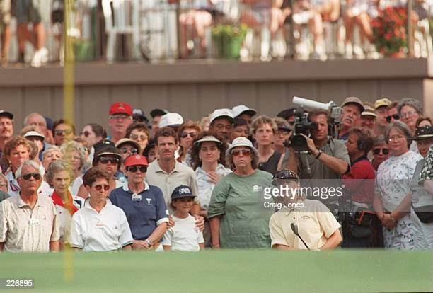 Spectators look on in the background as Annika Sorenstam of Sweden watches her ball hit the 18th green on her way to winning the 1996 US Womens Open...