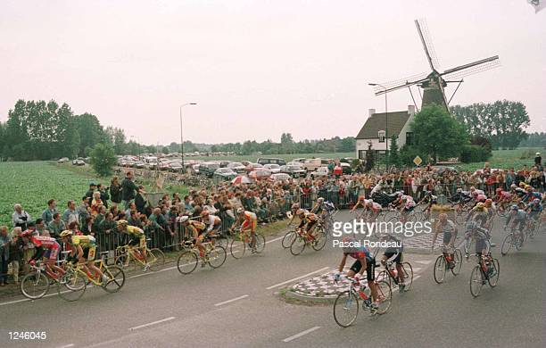 The Peleton in the early stages of the race pass a windmill on the first stage of the Tour De France which is 206 km around the town of...