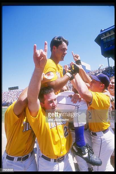 Warren Morris of the Miami Hurricanes rides on top of his teammates after winning a playoff game against the Louisville Cardinals at Rosenblatt...